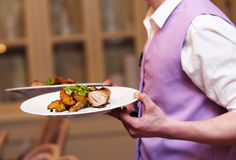 Waiter carrying two plate Stock Photography