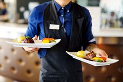 Waiter carrying two plates with meat dish on some festive event Stock Photo