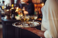 Waiter from catering service carrying champagne wine drinks on the tray at event. Stock Photos