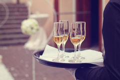 Waiter with 4 champagne glases. Waiter holding a tray with 4 champagne glasses Royalty Free Stock Photos