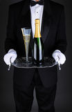 Waiter with Champagne on Tray. Closeup of a waiter with a bottle and flue of champagne on a silver serving tray. Vertical format over a light to dark gray Stock Image