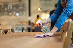Waiter cleaning the table with spray disinfectant on table in restaurant. Waiter cleaning the table with spray disinfectant on table in restaurant stock image