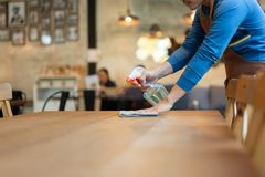 Waiter cleaning the table with spray disinfectant on table in restaurant.  stock photography