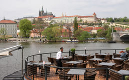 Waiter cleans tables at an outdoor restaurant on the riverbank of Vltava in Prague, with the Prague Castle in the background Stock Photo