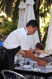 Waiter clearing tables, Malaga, Spain. Royalty Free Stock Images