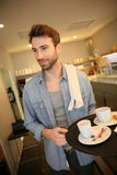 Waiter in a coffee shop serving his guests Royalty Free Stock Photo