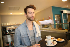 Waiter at the coffee shop serving Royalty Free Stock Image
