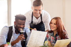 Waiter and couple with menu and drinks at bar Stock Photography