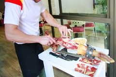 Waiter cuts the jamon at the entrance to the restaurant. Excelle