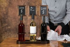 Waiter is decorating three wine bottles with a price board for s Royalty Free Stock Photography