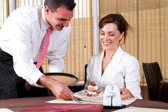 Waiter and diner. Handsome young waiter serving dessert to pretty young female diner in restaurant royalty free stock photo