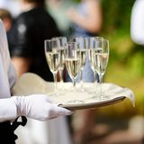 Waiter with dish of champagne glasses Stock Photo