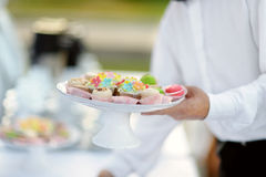 Waiter with dish of cupcakes Royalty Free Stock Images