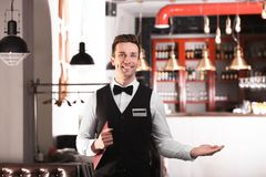Waiter in elegant uniform with menu Royalty Free Stock Photography