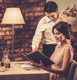 Waiter explaining the menu to a beautiful woman Stock Photos