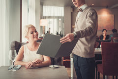 Waiter explaining menu to elegant woman in restaurant Royalty Free Stock Photography
