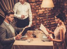 Waiter explaining the menu to stylish couple in restaurant. Royalty Free Stock Photo