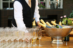 A waiter filled champagne glasses. Before him are many champagne glasses Stock Photos