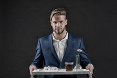 Waiter in formal suit. Bearded man hold tray with flower. Macho serve dessert food and drink. Service and restaurant catering conc. Ept. Womens day or 8 march Royalty Free Stock Images