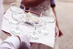 Waiter four glasses of champagne on table Stock Photography