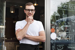 Waiter in front of the entrance of cafe Royalty Free Stock Image