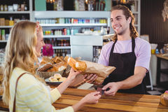 Waiter giving bread roll to customer at counter Stock Photo