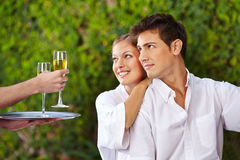 Waiter giving couple champagne Royalty Free Stock Photos