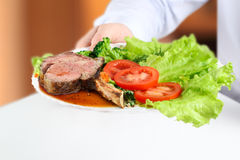 Waiter giving a Gorgeous Club steaks and vegetables on a plate Royalty Free Stock Images