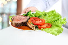 Waiter giving a Gorgeous Club steaks and vegetables on a plate Stock Photo