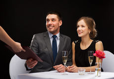 Waiter giving menu to happy couple at restaurant Stock Photo