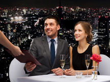 Waiter giving menu to happy couple at restaurant Stock Image