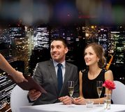 Waiter giving menu to happy couple at restaurant. Restaurant, couple and holiday concept - waiter giving menu to happy couple at restaurant Royalty Free Stock Image