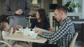 Waiter giving menu to happy family at cafe. Father consulting with him. stock video footage