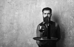 Waiter with glass and bottle of red wine on tray. Man with beard holds wine on beige wall background. Waiter with glass and bottle of red wine on tray.. Man with Stock Images