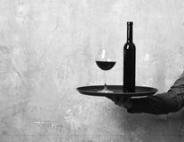 Waiter with glass and bottle of red wine on tray. Barmans hand holds and serves red wine. Service and catering concept. Male hand holds wine on beige wall Royalty Free Stock Images