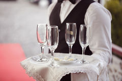 Waiter with glasses for champagne on tray Royalty Free Stock Photography