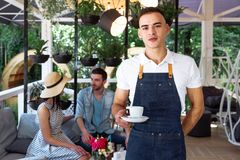 Waiter green white leaves coffee cup portrait young male barista service coffee customer cafe apron. A cute young waiter in a white T-shirt and a blue apron Royalty Free Stock Image