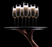 Waiter hand with champagne. On black background Royalty Free Stock Images