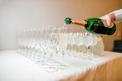 Waiter hand pouring champagne into glasses Stock Image