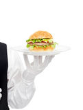 Waiter hand in white gloves holding hamburger on plate Stock Images