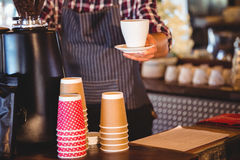 Waiter handing over a coffee Stock Photography