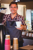 Waiter handing over a coffee Stock Images