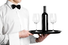 Waiter hands with wine bottle. Waiter hands with bottle of red wine and stemware glass on tray Royalty Free Stock Photos