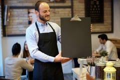 Waiter holding blackboard Stock Image