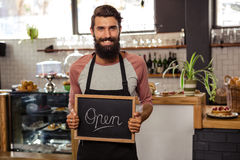 Waiter holding blackboard with open Royalty Free Stock Image