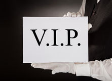 Waiter Holding Board With The Text Vip. Close-up Of Waiter In Uniform Holding Board With The Text Vip Royalty Free Stock Photography