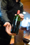 Waiter holding a bottle of red wine Royalty Free Stock Photo