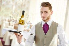 Waiter holding bottle of wine and glasses Stock Image