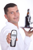 Waiter holding cell phone. Picture of waiter holding out cell phone Stock Images