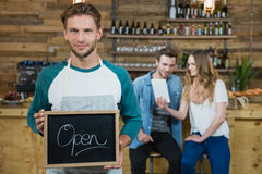 Waiter holding chalkboard with open sign and customer in background Royalty Free Stock Photo